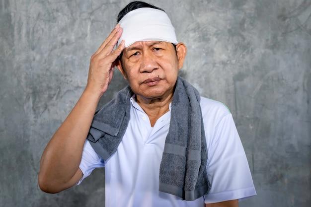 Senior aziatische man sportkleding in pijn met ernstig hoofdletsel. Premium Foto
