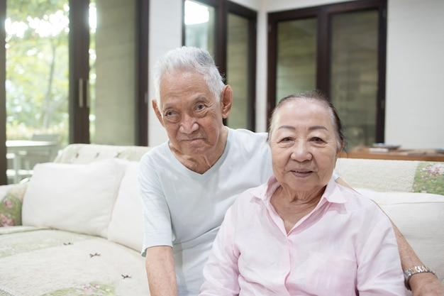 Senior aziatische paar omhelzen elkaar op de bank Premium Foto