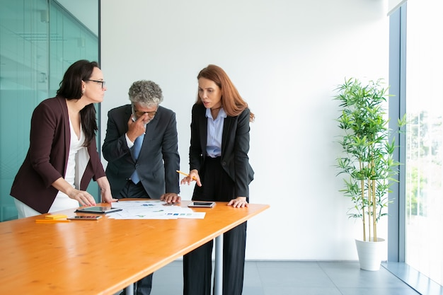 Senior baas in glazen kijken naar statistieken en project bespreken met partners. inhoud succesvolle ondernemers staan in de buurt van tafel met tabletten en papieren en praten. zaken en samenwerking con Gratis Foto