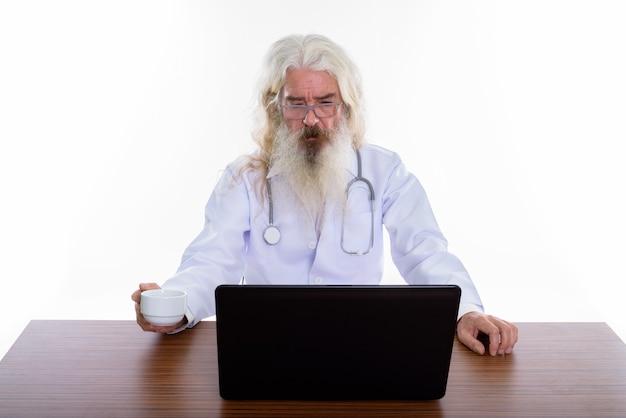 Senior bebaarde man arts bril dragen tijdens het gebruik van laptop Premium Foto
