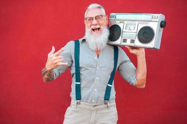 Senior gekke man met 80's boombox stereo die rockmuziek speelt met rode achtergrond - trendy volwassen man die plezier heeft met dansen met vintage radio - vrolijke levensstijlconcept voor ouderen - focus op zijn gezicht Premium Foto