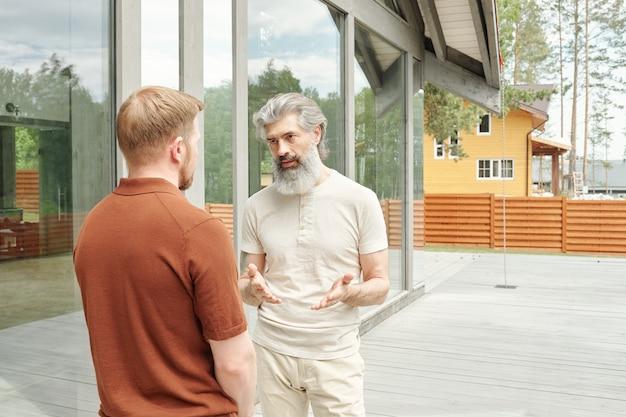 Senior grijsharige vader staande veranda van cottage huis en gebaren handen tijdens het praten met volwassen zoon Premium Foto