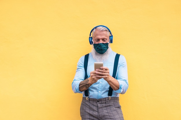 Senior hipster man met behulp van telefoon tijdens het luisteren afspeellijst muziek op mobiele app Premium Foto