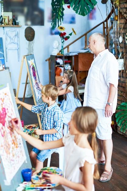 Senior kunstleraar werken met kinderen Premium Foto
