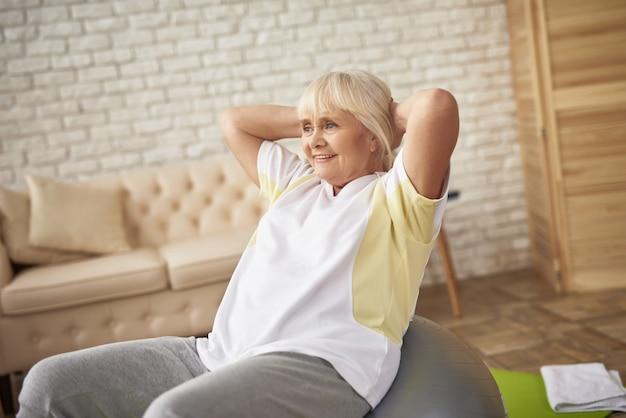 Senior lady doing press oefening op fitnessbal. Premium Foto