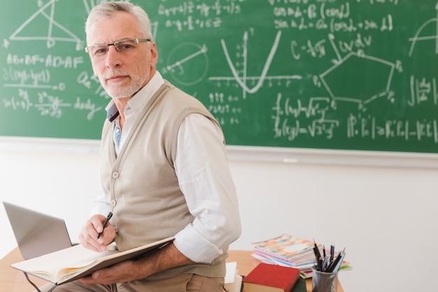 Senior leraar zittend op een bureau en schrijven in notitieblok Gratis Foto