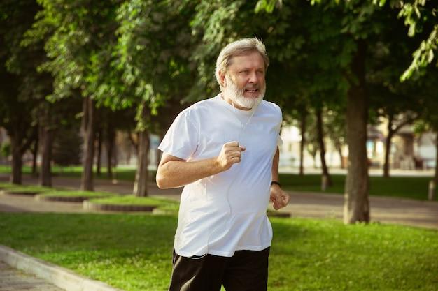 Senior man als hardloper met armband of fitnesstracker op straat in de stad. kaukasisch mannelijk model joggen en cardio-trainingen in de zomerochtend. gezonde levensstijl, sport, activiteitenconcept. Gratis Foto