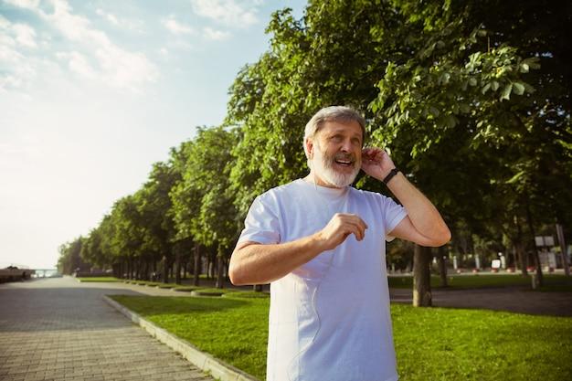 Senior man als hardloper met fitnesstracker op straat in de stad. kaukasisch mannelijk model dat gadgets gebruikt tijdens het joggen en cardiotraining in de zomerochtend. gezonde levensstijl, sport, activiteitenconcept. Gratis Foto