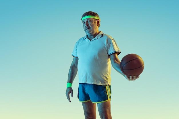 Senior man basketbal spelen op verloop achtergrond in neon licht. blank mannelijk model in uitstekende vorm blijft actief, sportief. Gratis Foto