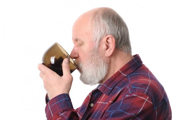 Senior man drinken uit de beker. Premium Foto