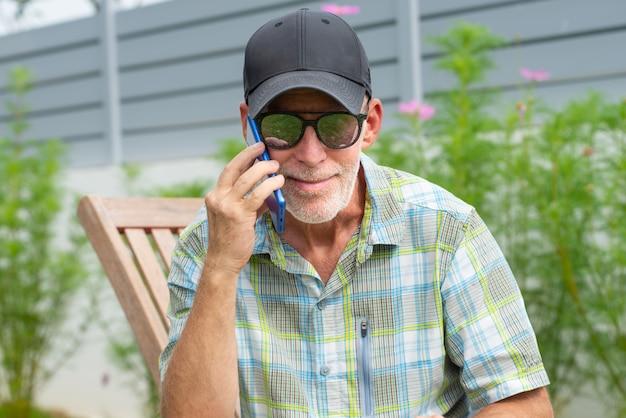 Senior man in een baseball cap portret met behulp van smartphone Premium Foto