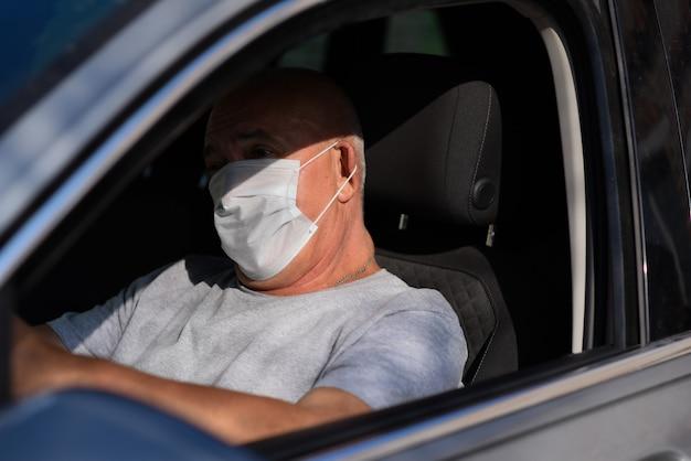 Senior man in medisch masker autorijden, kijkend naar de camera. coronavirus concept. Premium Foto