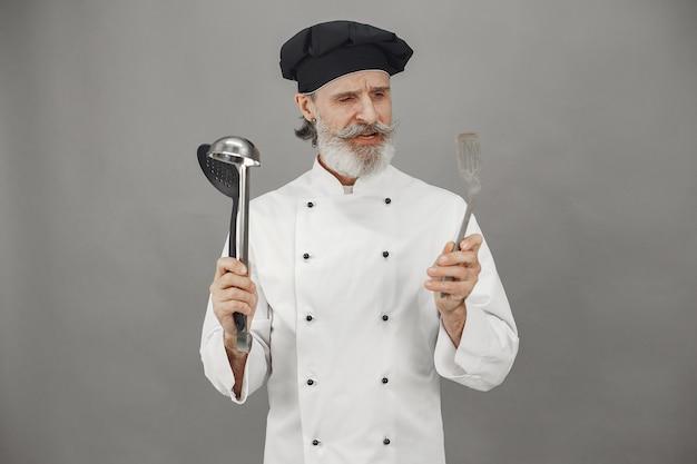 Senior man kiest pollepels. chef-kok in een zwarte pet in zijn hoofd. professionele benadering van zaken. Gratis Foto