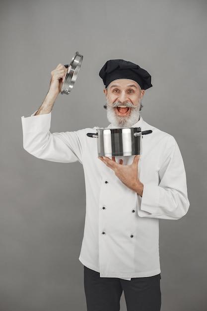 Senior man met metalen pan. chef-kok in een zwarte hoed. professionele benadering van zaken. Gratis Foto