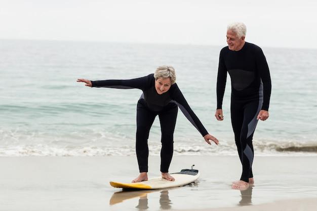 Senior man onderwijs vrouw om te surfen Premium Foto