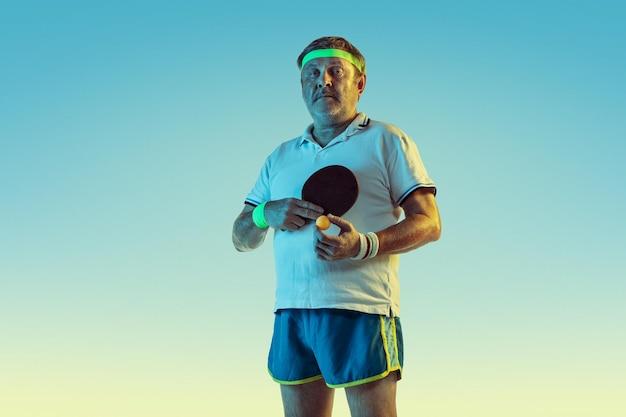 Senior man tafeltennis spelen op verloop achtergrond in neon licht. blank mannelijk model in uitstekende vorm blijft actief, sportief. Gratis Foto