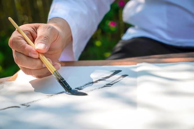Senior man tekening bamboeboom door azië china penseel met aziatische streekstijl. hij zit in de ontspannende bamboektuin. Premium Foto