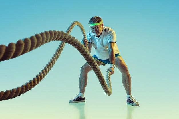 Senior man training met touwen op de achtergrond met kleurovergang in neonlicht. blank mannelijk model in uitstekende vorm blijft actief, sportief. Gratis Foto