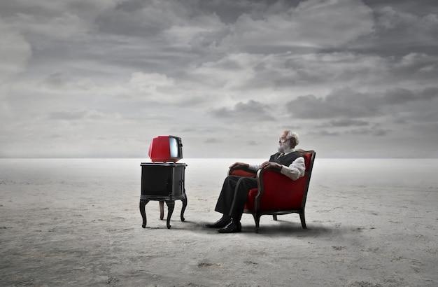 Senior man tv kijken vanuit een leunstoel Premium Foto