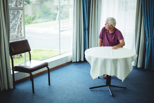 Senior man zit in de woonkamer Premium Foto