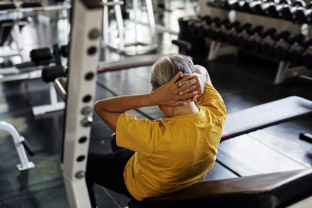 Senior man zitten in de sportschool Premium Foto