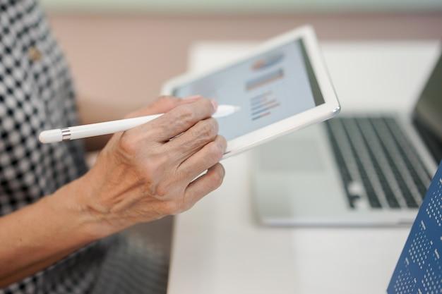 Senior manager zakenvrouw hand pen punt gebruiken op dashboard scherm tablet-apparaat Premium Foto