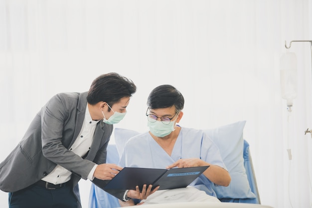 Senior mannen liggend op het bed tijdens de ziekenhuisvergadering met financieel adviseur, senior vrouw die contract leest. beiden droegen hygiënemaskers om uitbraken van ziekten te voorkomen. Premium Foto
