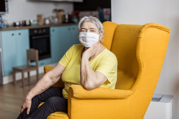 Senior oude vrouw in masker quarantaine europa. ouderen met risico op coronavirus covid-19. blijf thuis. chinese virus longontsteking pandemische bescherming grootmoeder. gevaar om besmet te raken Premium Foto