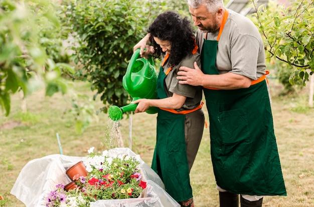 Senior paar bloemen water geven Gratis Foto