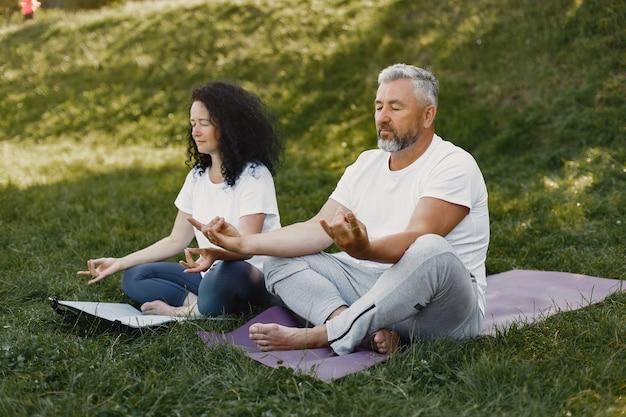 Senior paar doet yoga buitenshuis. die zich uitstrekt in het park tijdens zonsopgang. brunette in een wit t-shirt. Gratis Foto