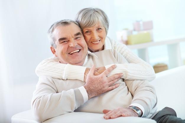 Senior paar knuffelen thuis Gratis Foto