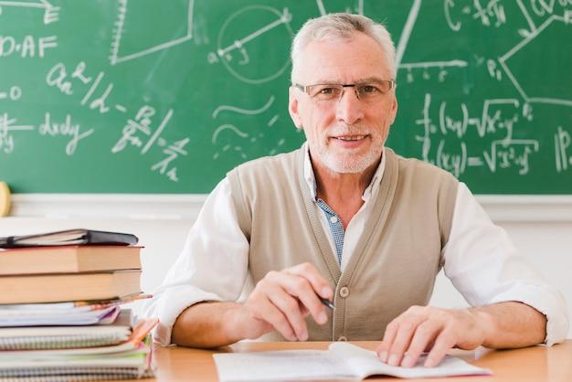 Senior professor zit aan bureau in de collegezaal Gratis Foto