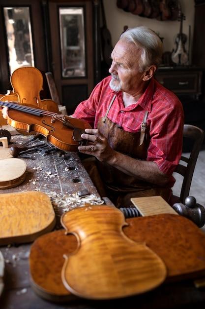Senior timmerman die vioolinstrument controleert dat hij op het punt staat te repareren Gratis Foto