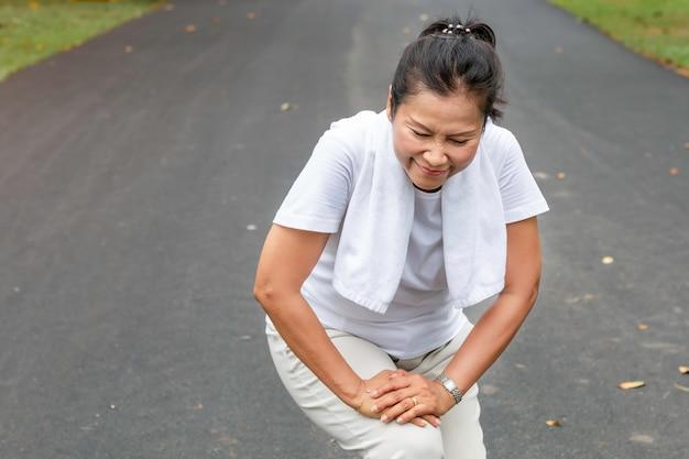 Senior vrouw aziatische been pijn tijdens het hardlopen in het park. Premium Foto
