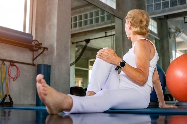 Senior vrouw doet yoga oefening op fitness gym. Premium Foto