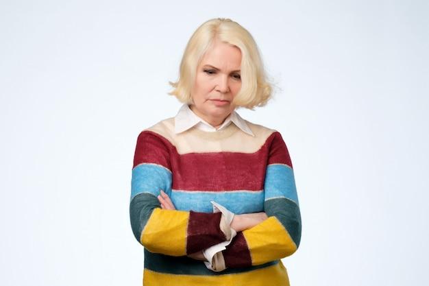 Senior vrouw houdt handen gekruist over borst, kijkt met droevige uitdrukking. Premium Foto
