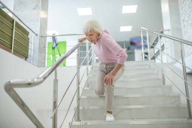 Senior vrouw in roze shirt vallen op de trap Premium Foto