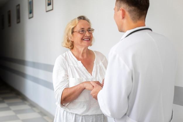 Senior vrouw met arts handen Gratis Foto