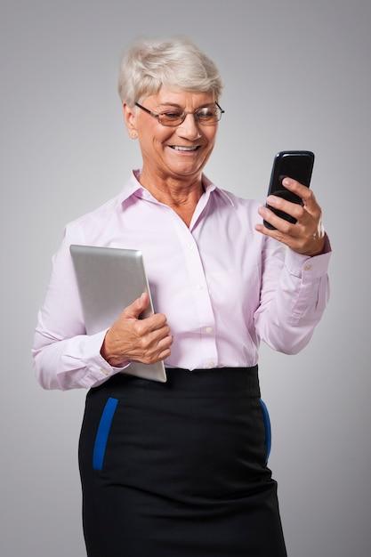 Senior vrouw met behulp van moderne technologie in haar bedrijf Gratis Foto