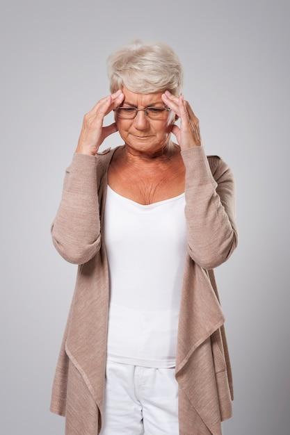 Senior vrouw met enorme pijn van het hoofd Gratis Foto