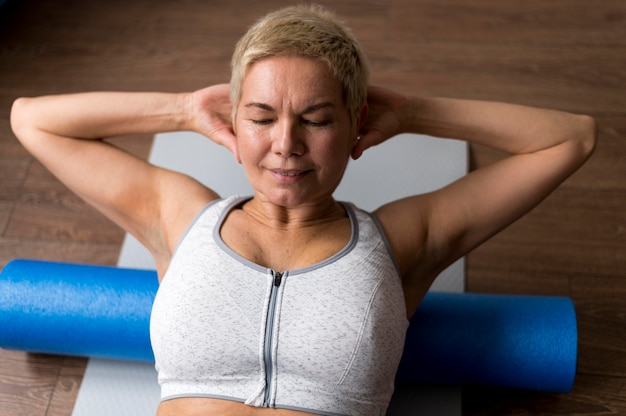 Senior vrouw met kort haar fitness doen Gratis Foto