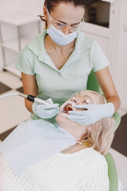 Senior vrouw met tandheelkundige behandeling op het kantoor van de tandarts. de vrouw wordt behandeld voor tanden Gratis Foto