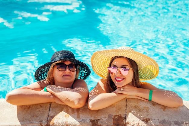Senior vrouw ontspannen met haar volwassen dochter in het zwembad van het hotel. mensen die van vakantie genieten. moederdag Premium Foto