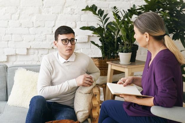 Senior vrouw psychotherapeut of adviseur iets opschrijven in notitieblok tijdens therapiesessie met gefrustreerde depressieve jonge man in bril. psychologie, counseling en geestelijke gezondheid Gratis Foto