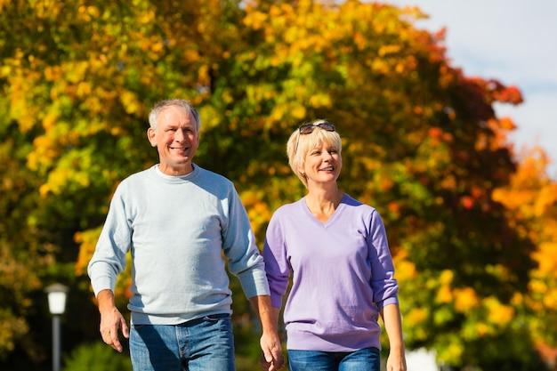 Senioren in de herfst of herfst lopen hand in hand Premium Foto