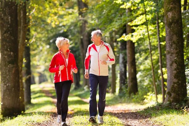 Senioren joggen op een bosweg Premium Foto