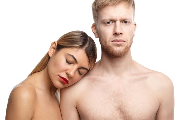 Sensueel gepassioneerd volwassen koppel poseren topless: knappe ongeschoren man kijkt met ernstige uitdrukking terwijl blonde vrouw ogen gesloten houden en hoofd op zijn schouder rusten Gratis Foto