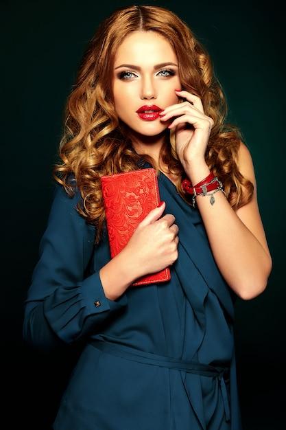 Sensueel glamourportret van mooi vrouwenmodel met verse dagelijkse make-up met rode lippenkleur en schone gezonde huid. met handtas in de hand Gratis Foto