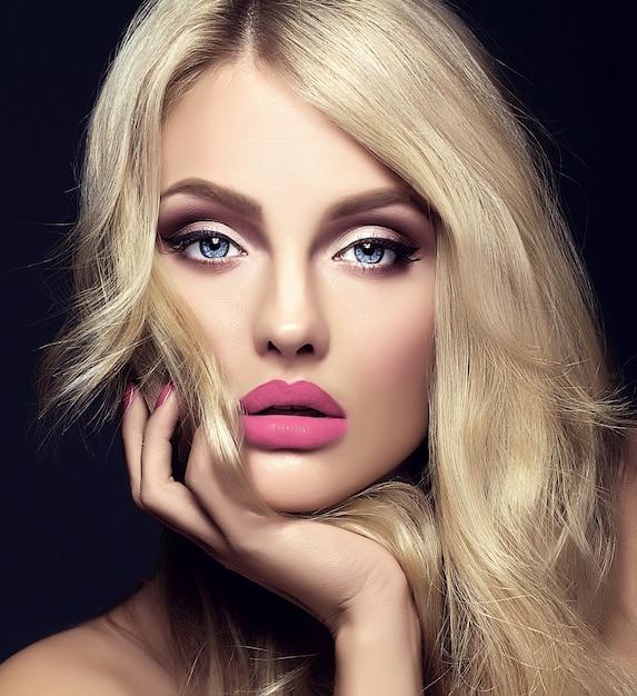 Sensueel glamourportret van mooie blonde vrouwmodel dame met lichte make-up en rode lippen wat betreft haar gezicht, met gezond krullend haar op zwarte achtergrond Gratis Foto