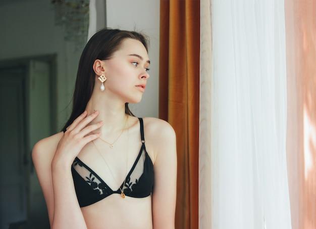 Sensueel jong mooi lang haarmeisje mannequin in ondergoed en jewerly dichtbij venster Premium Foto